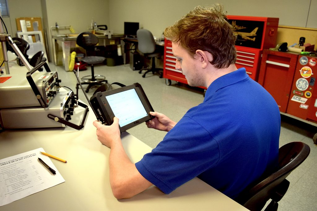 Texas State Technical College student in a blue t-shirt using T-RX avionic tester in classroom lab.